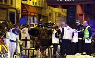 A general view of the scene shows rescue service personnel working near the covered bodies outside a restaurant following a shooting incident in Paris Friday. Photo by Philippe Wojazer
