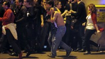 ATTENTION EDITORS - VISUAL COVERAGE OF SCENES OF INJURYAn injured man holds his head as people gather near the Bataclan concert hall following fatal shootings in Paris, France, November 13, 2015. At least 30 people were killed in attacks in Paris and a hostage situation was under way at a concert hall in the French capital, French media reported on Friday.  REUTERS/Christian Hartmann - RTS6W2R