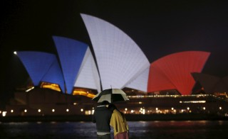 A couple stands in the rain as the colors of the French flag are projected onto Sydney's Opera House in Australia, November 14, 2015. Countries around the world used similar displays to show solidarity with France following a series of terrorist attacks in Paris Friday night. Photo by Jason Reed/Reuters