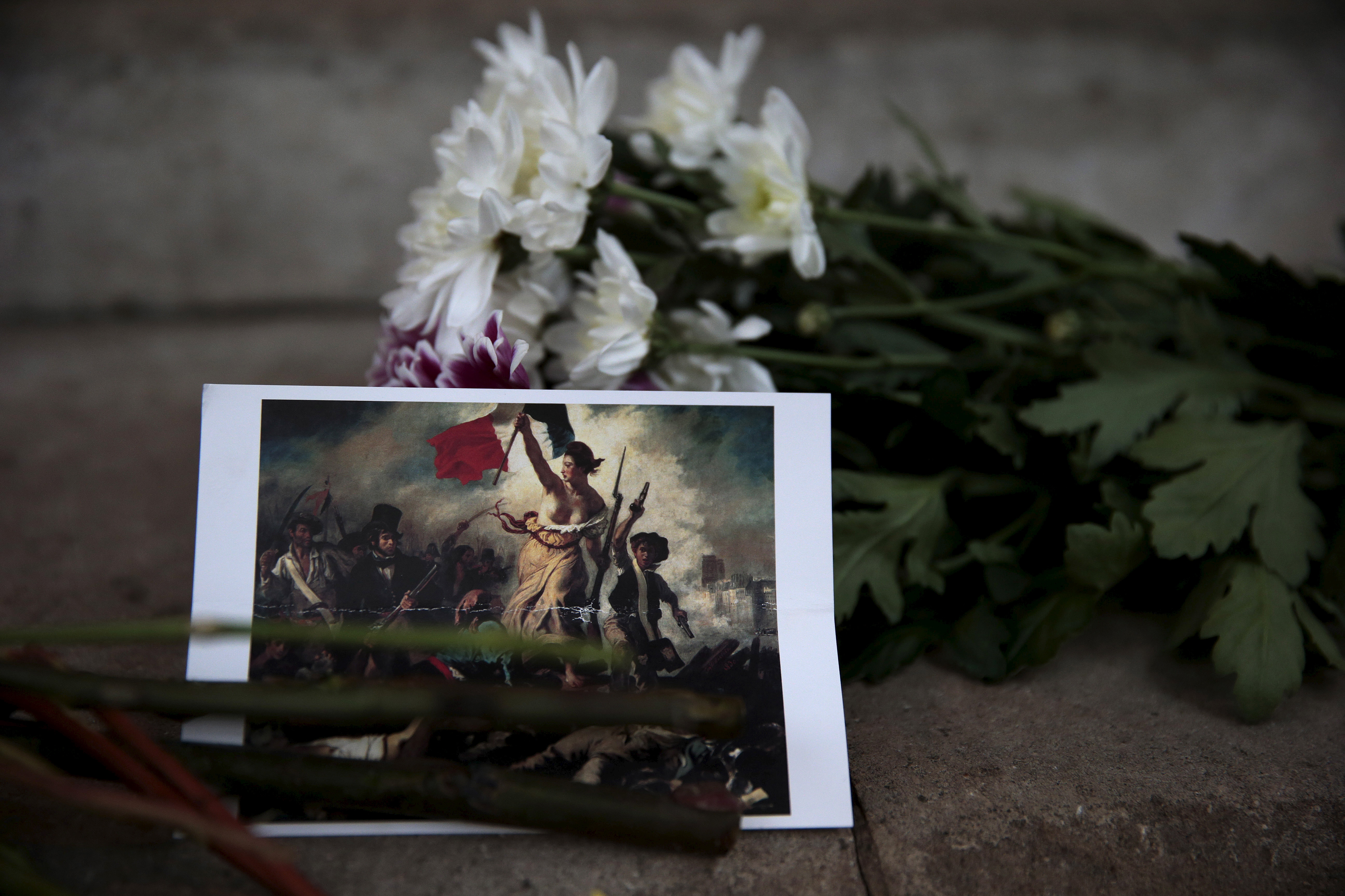 A postcard and flowers are left in tribute to victims of Paris attacks outside the French Embassy in London, Britain November 14, 2015. REUTERS/Suzanne Plunkett - RTS6Z8C