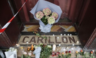 Flowers are seen placed on the doorstep of the Le Carillon restaurant the morning after a series of deadly attacks in Paris , November 14, 2015.      REUTERS/Christian Hartman - RTS6ZE8