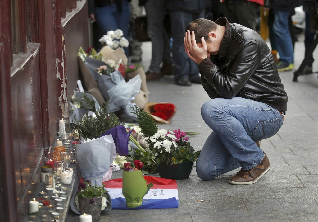 A man pays his respects on Nov. 14 outside the Le Carillon restaurant, one of the sites of a deadly assault in Paris the previous night. Photo by Christian Hartman/Reuters
