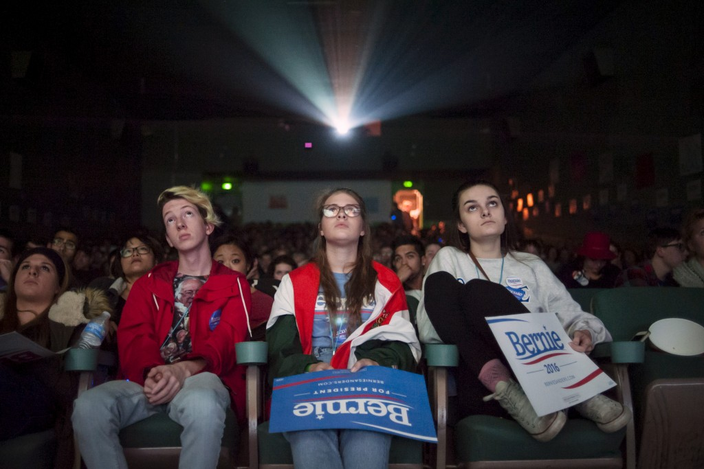 Jonah Guy (L), Deni Baird, and Lenin Cardwell watch a movie screen at a debate watch event in support of Democratic U.S. presidential candidate Bernie Sanders in Des Moines, Iowa in November.  Photo by Mark Kauzlarich/Reuters