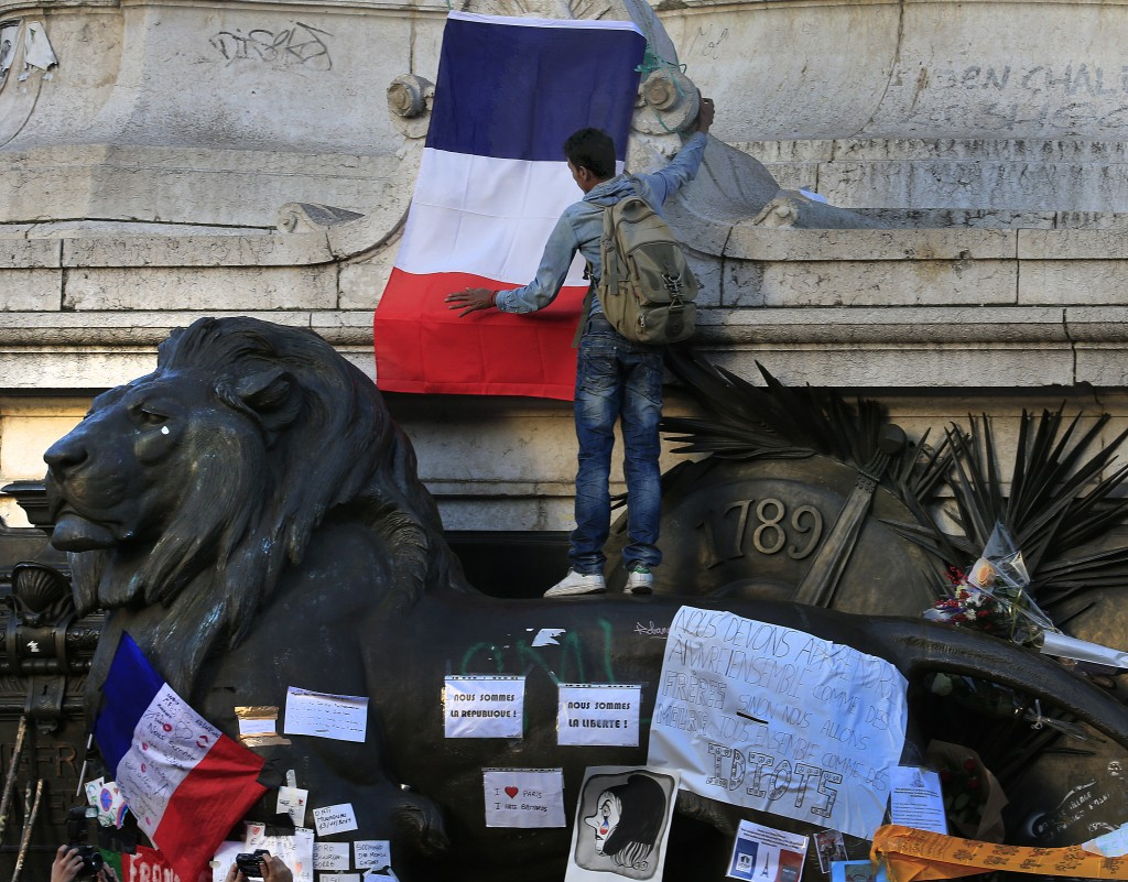 A man attaches a French flag to a statue at Place de la Republique near sites of the deadly attacks in Paris, November 15, 2015. Photo by   Pascal Rossignol/Reuters