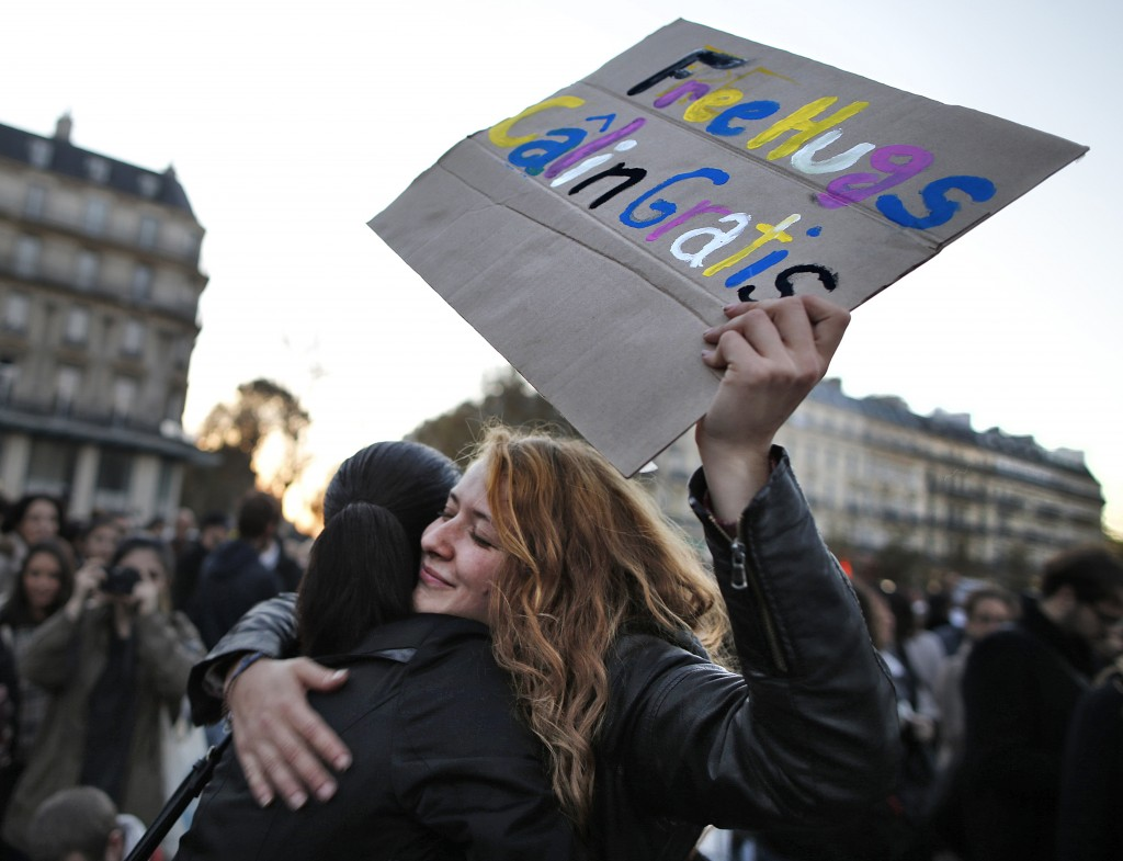 A woman offers free hugs as people gather in Place de la Republique after the series deadly attacks in Paris, November 15, 2015. Photo by Christian Hartmann/Reuters