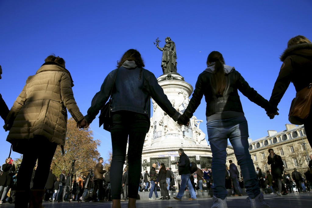 People hold hands to form a human solidarity chain near the site of the attack at the Bataclan concert hall in Paris, November 15, 2015. Photo by Pascal Rossignol/Reuters