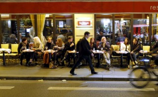 A man walks on the street as people sit at a table outside a bistro in Paris, France, November 18, 2015. Parisians were called to flock en masse to the French capital's renowned cafes and restaurants after last week's attacks that killed many cafe-goers.   REUTERS/Gonzalo Fuentes - RTS7UDQ