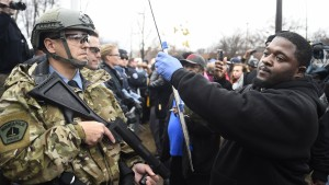 Police officers watch as a demonstrator holds a sign in front of a north Minneapolis police precinct during a protest in response of Sunday's shooting death of Jamar Clark by police officers in Minneapolis, Minnesota, November 18, 2015. Minnesota officials on Wednesday identified the two Minneapolis police officers involved in the fatal shooting of an unarmed black man as chanting demonstrators surrounded a key police station.     REUTERS/Craig Lassig - RTS7ULH