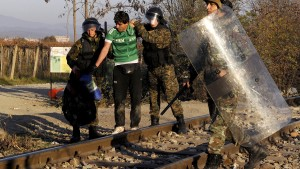 An Iranian migrant is escorted back to Greece by Macedonian policemen after he tried to cross Greece's border with Macedonia illegally, near the Macedonian town of Gevgelija, November 19, 2015. Balkan countries have begun filtering the flow of migrants to Europe, granting passage to those fleeing conflict in the Middle East and Afghanistan but turning back others from Africa and Asia, the United Nations and Reuters witnesses said on Thursday. Picture taken from the Greek side of the Greek-Macedonian border near the Greek village of Idomeni. REUTERS/Alexandros Avramidis      TPX IMAGES OF THE DAY      - RTS7XFF