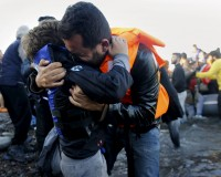 A Syrian refugee embraces his son after their overcrowded raft landed at a rocky beach in the Greek island of Lesbos, November 19, 2015. Balkan countries have begun filtering the flow of migrants to Europe, granting passage to those fleeing conflict in the Middle East and Afghanistan but turning back others from Africa and Asia, the United Nations and Reuters witnesses said on Thursday. REUTERS/Yannis Behrakis - RTS7Z74