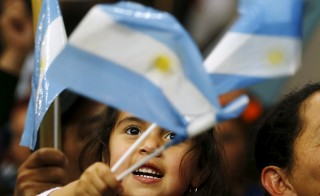 A child waves Argentine national flags during the final campaign rally of Argentina's ruling party candidate Daniel Scioli in La Matanza, on the outskirts of Buenos Aires, Nov. 19, 2015. Marcos Brindicci/Reuters