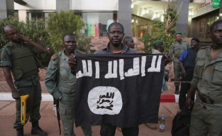 Malian security officials show a jihadist flag they said belonged to attackers in front of the Radisson hotel in Bamako, Mali, November 20, 2015. REUTERS/Joe Penney      TPX IMAGES OF THE DAY      - RTS863H
