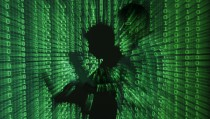 An illustration picture shows a projection of binary code on a man holding a laptop computer, in an office in Warsaw June 24, 2013. REUTERS/Kacper Pempel (POLAND - Tags: BUSINESS TELECOMS TPX IMAGES OF THE DAY) - RTX10ZB5