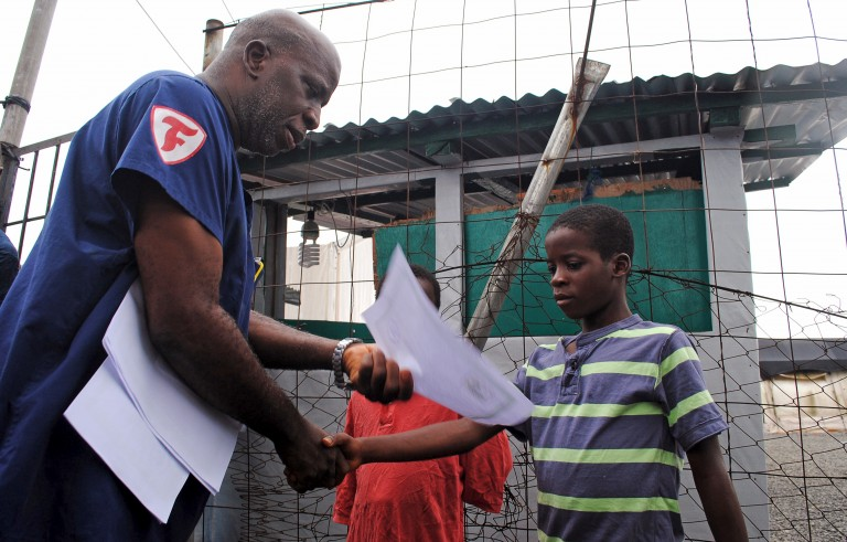 Moses Duo, 9, receives a certificate for being cured of the Ebola virus in Paynesville, Liberia, July 20, 2015. The last four cases of Ebola in Liberia were discharged from a treatment clinic on Monday, meaning there were no more confirmed carriers of the deadly virus in the West African country. REUTERS/James Giahyue  - RTX1L2AA