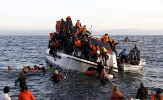 Refugees, most of them Syrians, struggle to leave a half-sunken catamaran carrying around 150 refugees as it arrives on the Greek island of Lesbos, after crossing part of the Aegean sea from Turkey,  October 30, 2015. There were no casaulties amongst the refugees who were travelling on the catamaran, according to a Reuters witness. The death toll from drownings at sea has mounted recently as weather in the Aegean has taken a turn for the worse, turning wind-whipped sea corridors into deadly passages for thousands of refugees crossing from Turkey to Greece.  REUTERS/Giorgos Moutafis - RTX1TXBD