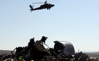An Egyptian military helicopter flies over debris from a Russian airliner which crashed at the Hassana area in Arish city, north Egypt, November 1, 2015. Russia has grounded Airbus A321 jets flown by the Kogalymavia airline, Interfax news agency reported on Sunday, after one of its fleet crashed in Egypt's Sinai Peninsula, killing all 224 people on board. REUTERS/Mohamed Abd El Ghany - RTX1U8ZT