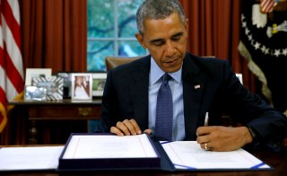 President Barack Obama signs the Bipartisan Budget Act of 2015 into law in the Oval Office. Photo by Jonathan Ernst/Reuters