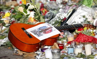 "A guitar with a message bearing France's national motto ""Liberte, Egalite, Fraternite"", is seen among flowers left in tribute to victims near the Bataclan concert hall, one of the sites of last Friday's deadly attacks, in Paris, France, November 21, 2015.   REUTERS/Charles Platiau - RTX1V583"
