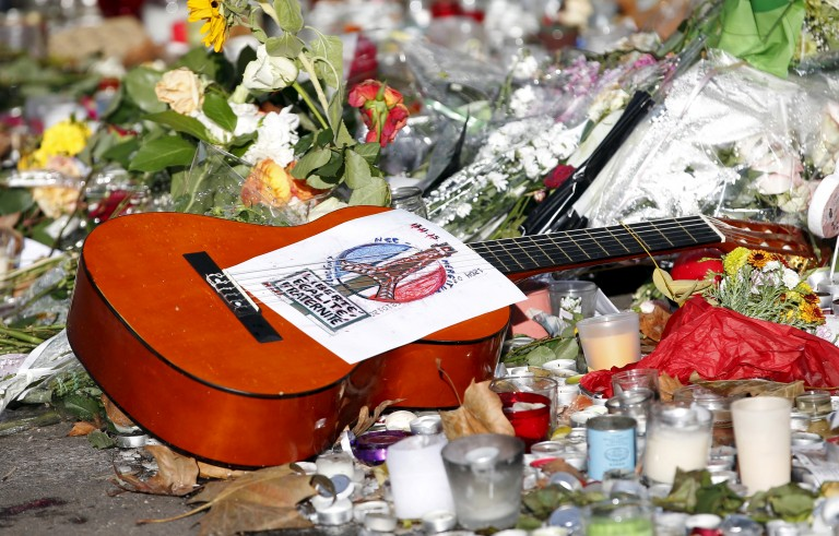 """A guitar with a message bearing France's national motto """"Liberte, Egalite, Fraternite"""", is seen among flowers left in tribute to victims near the Bataclan concert hall, one of the sites of last Friday's deadly attacks, in Paris, France, November 21, 2015.   REUTERS/Charles Platiau - RTX1V583"""