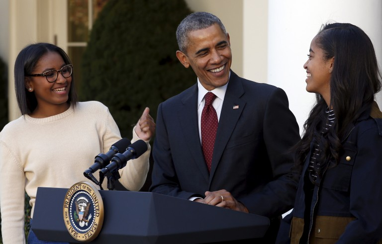 President Barack Obama smiles next to his daughters Sasha, left, and Malia at the pardon of the National Thanksgiving Turkey event in the Rose Garden of the White House in Washington November 25, 2015. Photo by Carlos Barria/Reuters