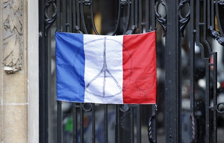 A French flag with the sign of a peace symbol with the Eiffel Tower is seen at the main entrance of an apartment building in Paris, France November 26, 2015. The French President called on all French citizens to hang the tricolour national flag from their windows on Friday to pay tribute to the victims of the Paris attacks.   REUTERS/Charles Platiau - RTX1VYFM