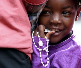 A child holds rosary beads before Pope Francis' arrival at the Kangemi slums on the outskirts of Kenya's capital Nairobi, November 27, 2015. REUTERS/Stefano Rellandini - RTX1W273