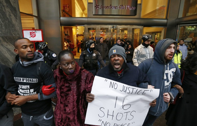 """Demonstators link arms in solidarity as they protest last year's shooting death of black teenager Laquan McDonald by a white policeman and the city's handling of the case in the downtown shopping district of Chicago, Illinois, November 27, 2015. About 2,000 people with signs reading """"Stop Police Terror"""" gathered in a cold drizzle for the march on Chicago's """"Magnificent Mile"""" on the Black Friday shopping day, which was led by activist-politician the Rev. Jesse Jackson and several state elected officials. REUTERS/Jim Young  - RTX1W6AN"""