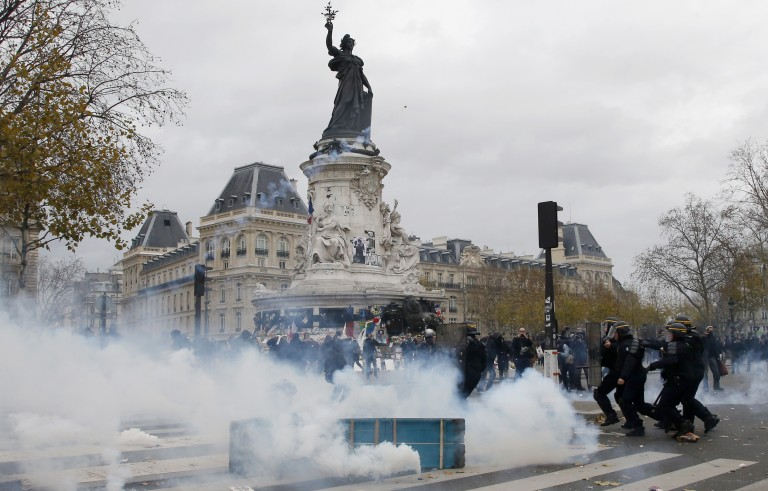Clouds of tear gas fill the air as demonstrators clash with French CRS riot police at the Place de la Republique after the cancellation of a planned climate march following shootings in the French capital, ahead of the World Climate Change Conference 2015 (COP21), in Paris, France, November 29, 2015.    REUTERS/Eric Gaillard - RTX1WCME