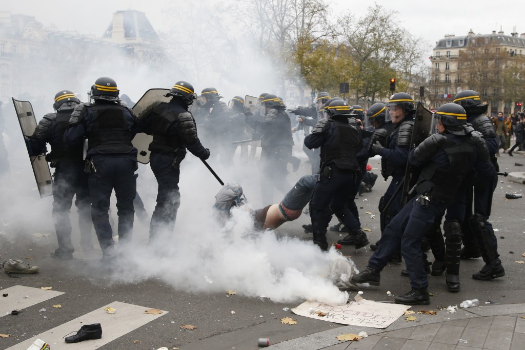 French CRS riot police apprehend a demonstrator during clashes near the Place de la Republique after the cancellation of a planned climate march following shootings in the French capital, ahead of the World Climate Change Conference 2015 (COP21), in Paris, France, November 29, 2015.     REUTERS/Eric Gaillard     - RTX1WCS1