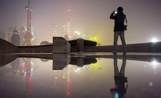 A man uses his mobile phone to take pictures of the financial area of Pudong New District (rear) on a smoggy day in Shanghai, China, November 30, 2015. Heavy smog and thick fog engulfed many parts of northern and eastern China on Monday, local media reported. REUTERS/Stringer CHINA OUT. NO COMMERCIAL OR EDITORIAL SALES IN CHINA       TPX IMAGES OF THE DAY      - RTX1WF9W