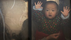A baby looks through the window of a vehicle stranded on a highway between Beijing and Hebei province, China, that is closed due to smog on an extremely polluted day November 30, 2015. REUTERS/Damir Sagolj - RTX1WFY8