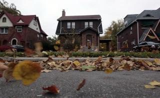 Fall leaves blow past an empty home (C) seen in a well kept neighborhood where the house is listed on the auction block during the Wayne County tax foreclosures auction of almost 9,000 properties in Detroit, Michigan, October 22, 2009. The tax foreclosure auction stood as one of the most ambitious one-stop attempts to sell of urban property since the real-estate market collapse. Picture taken October 22, 2009.  REUTERS/Rebecca Cook (UNITED STATES BUSINESS) - RTXQ08W