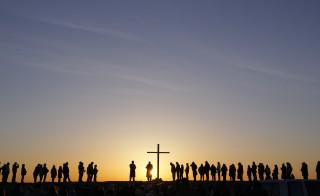 People are silhouetted as the sun rises during an Easter sunrise service in Scituate, Massachusetts March 31, 2013. Photo by Jessica Rinaldi/Reuters