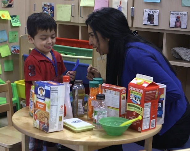 Teacher Lori Espinoza (right) uses environmental print in her classroom at the Gabriela Mistral Center for Early Childhood in Houston to help children with their language skills. Photo by Mike Fritz/PBS NewsHour