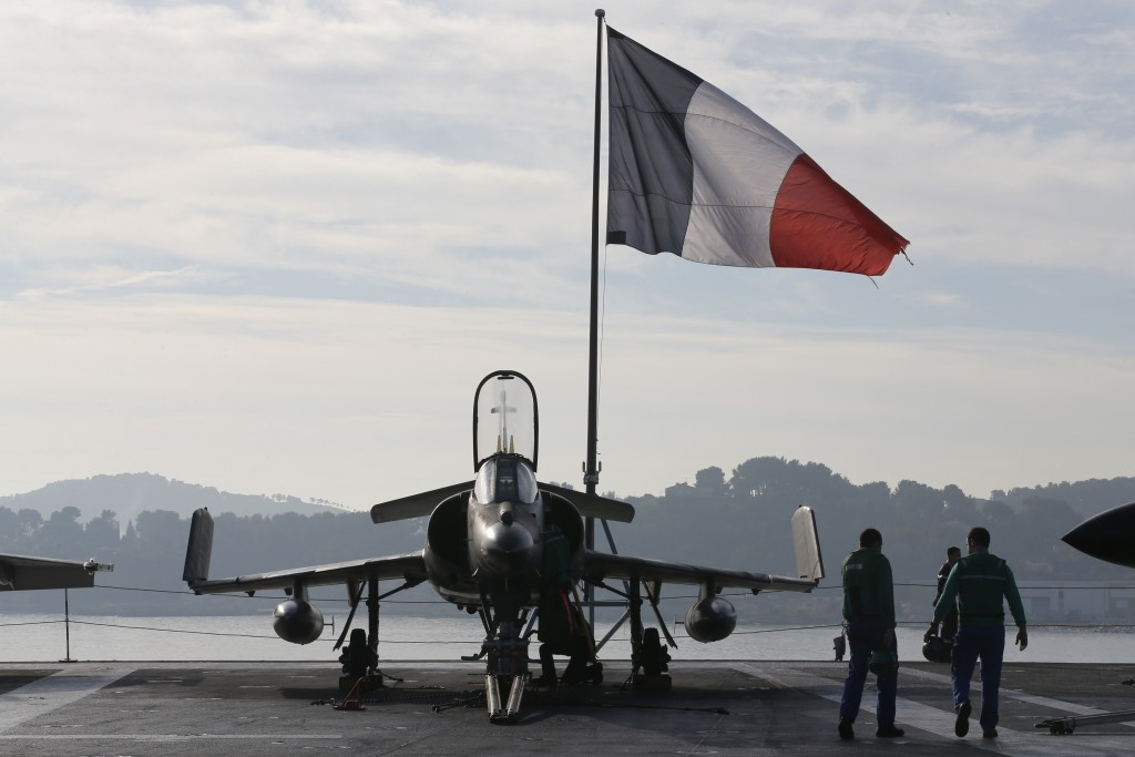 Flight deck crew work around a Super Etendard jet fighter aboard the French nuclear-powered aircraft carrier Charles de Gaulle before its departure from the naval base of Toulon, France, on Nov. 18, 2015. The aircraft carrier supported operations against Islamic State in Syria and Iraq. Photo by Jean-Paul Pelissier/Reuters
