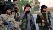 A man (center) identified as Al Karar the Iraqi, an Islamic State fighter, speaks at an undisclosed location in this image taken from undated video footage released by the Islamic State group. The group warned in the video on Nov. 16, 2015 that countries taking part in airstrikes against Syria would suffer the same fate as France, and threatened to attack in Washington, D.C. Screen image from Reuters