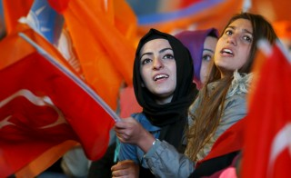 Women wave flags outside the AK Party headquarters in Ankara, Turkey on Nov. 2. Photo by Umit Bektas/Reuters