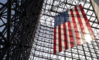 American Flag hanging from structure with sun behind