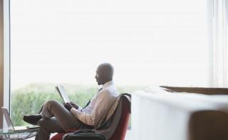 Businessman reading newspaper in hotel lobby