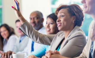 businesswoman raising hand, asking question in business conference