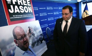 Ali Rezaian looks at a picture of his brother, Washington Post Tehran bureau chief Jason Rezaian, after a news conference at the National Press Club July 22, 2015 in Washington, DC. The news conference was to give an update on the case of Jason Rezaian, who is being held in Evin Prison in Iran since July 22, 2014.  Photo by Alex Wong/Getty Images