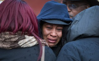 Janet Cooksey is comforted as she listens to speakers talk about the deaths of her son Quintonio LeGrier, and Bettie Jones before the start of a vigil on Saturday in Chicago. Photo by Scott Olson/Getty Images