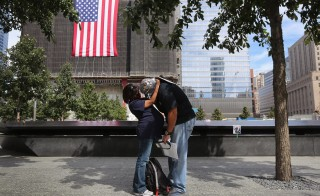 Jillian and Eloy Suarez embrace following ceremonies marking the 11th anniversary of the 9/11 attacks on the World Trade Center in New York, September 11, 2012. Eloy Suarez was a first responder during the 9/11 attacks. REUTERS/John Moore/POOL (UNITED STATES  - Tags: DISASTER ANNIVERSARY)   - RTR37U05
