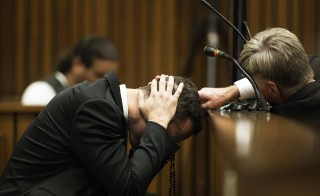 A member of the defence legal team reaches out to Olympic and Paralympic track star Oscar Pistorius as he holds his head while a witness testifies during the fourth day of his trial for the murder of his girlfriend Reeva Steenkamp at the North Gauteng High Court in Pretoria, March 6, 2014. REUTERS/Marco Longari/Pool (SOUTH AFRICA - Tags: SPORT ATHLETICS CRIME LAW TPX IMAGES OF THE DAY) - RTR3G431