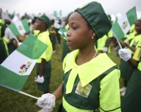 A school girl holds a Nigerian flag as she joins a parade marking Nigeria's 54th Independence Day in Lagos October 1, 2014. REUTERS/Akintunde Akinleye (NIGERIA - Tags: POLITICS ANNIVERSARY) - RTR48JM4