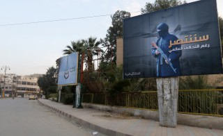 """Islamic State billboards are seen along a street in Raqqa, eastern Syria, which is controlled by the Islamic State, October 29, 2014. The billboard (R) reads:  """"We will win despite the global coalition"""". REUTERS/Nour Fourat  (SYRIA - Tags: POLITICS CIVIL UNREST CONFLICT MILITARY) - RTR4C21W"""