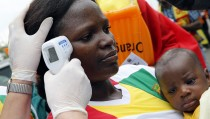 A health worker checks the temperature of a fan of Guinea at Malabo Stadium, ahead of their Group D soccer match against Ivory Coast in the African Cup of Nations, in Malabo January 20, 2015.  REUTERS/Amr Abdallah Dalsh (EQUATORIAL GUINEA - Tags: SPORT SOCCER HEALTH) - RTR4M6XG