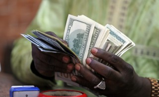 "A bureau de change operator counts U.S. currency notes in Abuja, March 12, 2015. In Nigeria, holding naira has become increasingly unpopular as it has lost its value. Basic everyday goods can still be paid for in the local currency but many items are scarce and Nigerians need U.S. dollars for imports such as drugs or fabrics sold by small-time traders, to send money to relatives abroad or to purchase western clothes that are important status symbols. Faced with a massive drop in oil revenues and declining reserves, Nigeria's central bank devalued the naira and then imposed rules restricting access to dollars to all but importing companies to curb what it termed ""speculation"". Picture taken March 12, 2015. REUTERS/Afolabi Sotunde (NIGERIA - Tags: BUSINESS POLITICS) - RTR4T8HA"