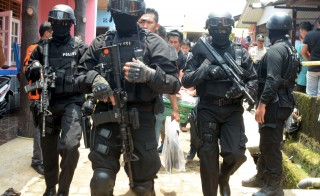 Armed anti-terror police walk ahead of guard officers in March carrying bags of evidence from the house of a man suspected of being involved in Islamic State-related activities in Indonesia. On Sunday, squad members arrested several more suspects accused of planning attacks. Photo by  Muhammad Iqbal/Reuters.