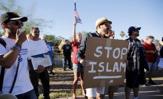 "Demonstrators shout during a ""Freedom of Speech Rally Round II"" outside the Islamic Community Center in Phoenix, Arizona May 29, 2015. More than 200 protesters, some armed, berated Islam and its Prophet Mohammed outside an Arizona mosque on Friday in a provocative protest that was denounced by counterprotesters shouting ""Go home, Nazis,"" weeks after an anti-Muslim event in Texas came under attack by two gunmen.    REUTERS/Nancy Wiechec - RTR4Y3N8"